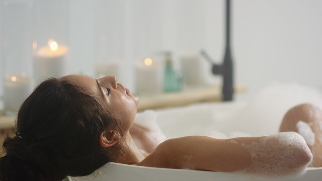 Close up relaxed woman lying in bath foam. Romantic girl relaxing at bathtub