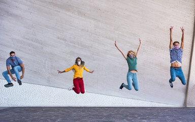 Young people jumping dancing outdoor during coronavirus outbreak - Happy friends wearing face...