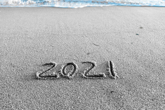 2021 year drawing on the sand at the beach.