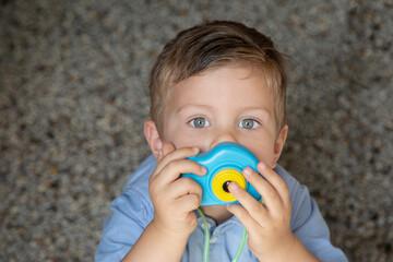 Bambino biondo con gli occhi azzurri tien in mano una macchina fotografica giocattolo