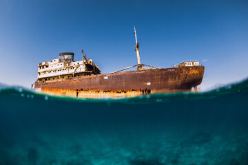 Photo Blinds Shipwreck Telamon wreck ship in blue ocean. Split shot. Lanzarote