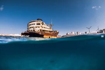 Garden Poster Shipwreck Telamon wreck ship in blue ocean. Split shot. Lanzarote