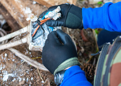 Electrician repairs the electrical connection of cables in an electrical junction box sealed with insulating gel to ensure protection of electrical cables from water