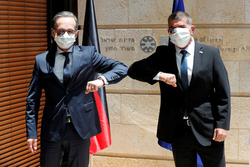 Israeli Foreign Minister Gabi Ashkenazi and his German counterpart Heiko Maas wear masks bearing their national flags to curb the spread of the coronavirus disease (COVID-19) as they greet each other during their meeting in Jerusalem
