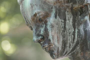 Nahaufnahme einer weiblichen Bronzestatue Frau mit kurzen Haaren mit Kreuz und Strickjacke in einem Park, Deutschland