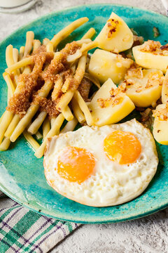 Fried eggs with boiled potatoes and yellow string beans