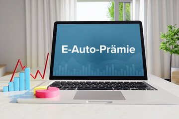 E-Auto-Prämie – Business/Statistik. Laptop im Büro auf Schreibtisch neben Diagramm. Text auf Monitor. Finanzen, Wirtschaft, Analyse