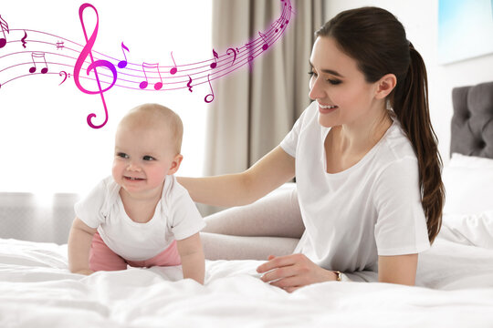 Flying music notes and little baby crawling near mother on bed indoors. Lullaby songs