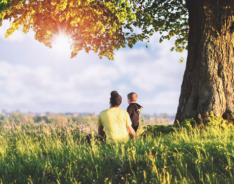 Dad with son in the spring meadow sitting under the tree in tall grass. Travel with child concept