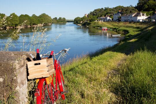 Paysage de bord de la Loire en Anjou, vélo du vigneron et ses bouteilles de vin.