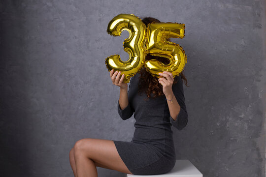 35 years old, beautiful sexy woman holding gold balloons, birthday celebration party