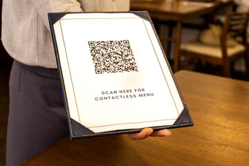 Waitress display contactless menu with QR code as part of new normal. QR code edited and not valid