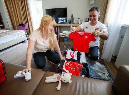 Jose Perez and Flavia Lavorino from Buenos Aires pack baby clothes before meeting their son for the first time, in Kiev