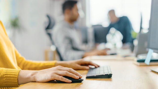 Anonymous Young Woman Sitting at Her Desk Using Laptop Computer. Focus on Hands Typing on Keyboard. In the Background Bright Office where Diverse Team of Young Professionals Work.