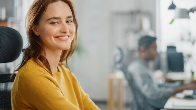 Portrait of Beautiful Young Woman with Red Hair Wearing Yellow Sweater Chats with Colleague and Turns Smilingly at Camera. Successful Woman Working in Bright Diverse Office.