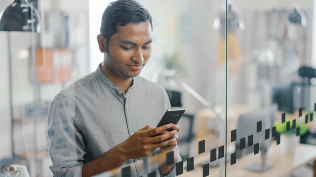 Portrait of Handsome Professional Indian Man Uses Mobile Phone, Writes Important Email. Successful Man Using Smartphone Working in Bright Diverse Office.