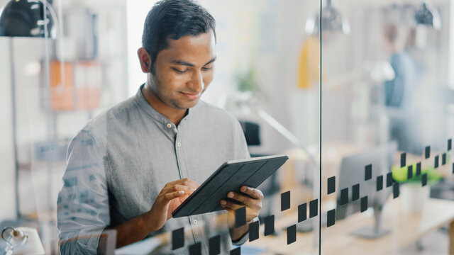 Portrait of Handsome Professional Indian Man Uses Touch Screen Digital Tablet Computer, Writes Important Email, Smiles Charmingly. Successful Man Working in Bright Diverse Office.