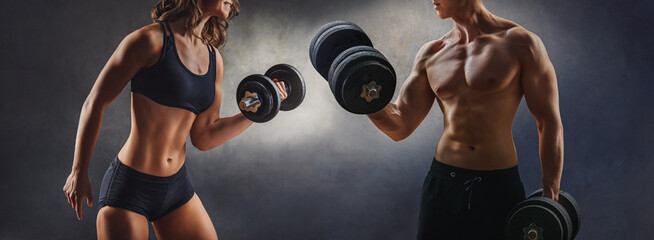 smiling woman an man with dumbbell - successful fitness studio concept
