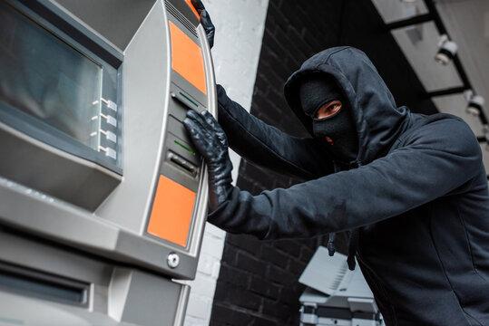 Selective focus of burglar in mask pulling atm