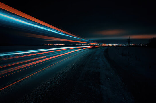 Long exposure of a road with light trails of passing vehicles, glowing sky