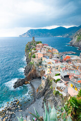 Foto auf Gartenposter Ligurien Vernazza, a traditional Italian village in National park Cinque Terre, in a cloudy daylight scene. Multicolored houses on rock cliff. Liguria, Italy