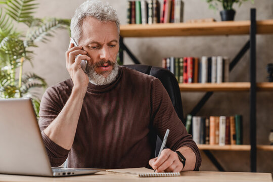 Handsome businessman in casual clothes talking on mobile phone and making notes while sitting in his office