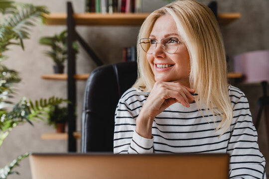 Happy senior woman holding pen daydreaming looking away sitting front of workplace