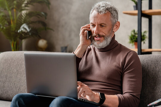 Handsome smiling middle aged businessman talking on mobile phone and using laptop while working at home