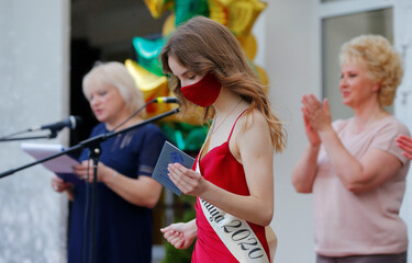 School graduate receives certificate during the graduation ceremony in Minsk