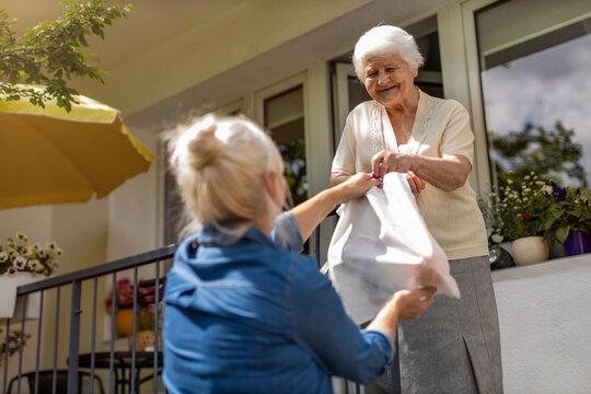 Adult daughter delivering groceries to her elderly mother