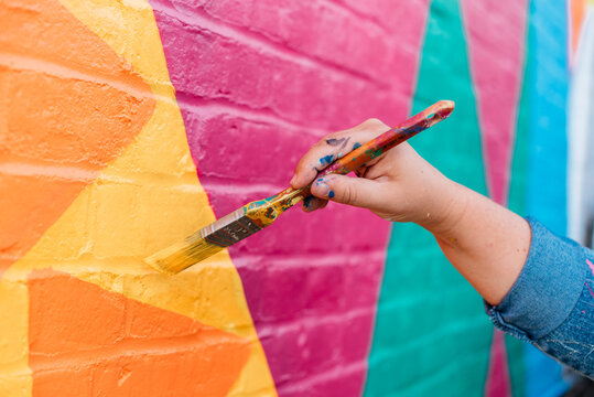 Artist painting a wall with a brush