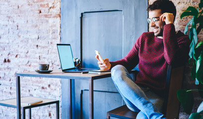 .Bearded freelancer in eyeglasses typing text information on digital laptop sitting in coworking Wall mural