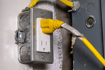Yellow electrical cord plugged into a metal outlet box