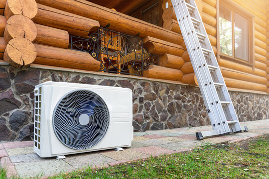 New modern HVAC air conditioning external compressor unit preapred for installation or replacement near wall of wooden log residential country cottage. Ladder and equipment for service and maintenance