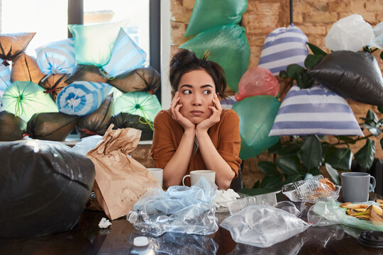 Asian woman spending time at her apartment full of rubbish