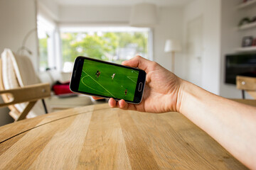 A male hand holding a smartphone which displays a soccer match on the touch screen. The big green screen is in contrast with the overexposed background. An image on an interior background.