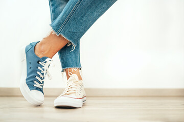 Wall Mural - Teenager's feet posing in casual different colors beige and blue new sneakers on the white wooden floor close up image. Vintage style in modern fashion world concept image.