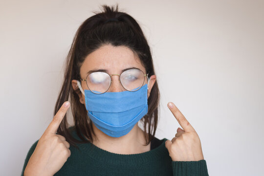young woman with mask and foggy glasses