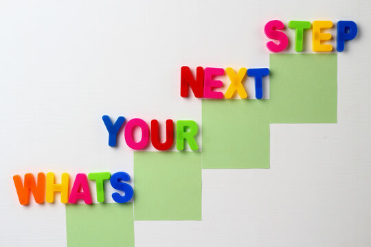 Text made in multicolored magnetic letters. WHATS YOUR NEXT STEP. White wooden