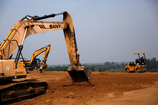 Workers operate excavators to prepare land for a new pig farm in Beijing's eastern Pinggu district