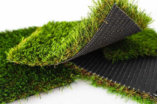 Sample pieces of green artificial grass of different thickness.