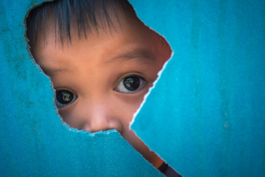portrait of young small autistic child face looking through cracked blue plastic wall background