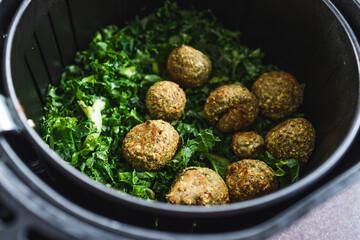 plant-based food, falafels and kale chips in air fryer