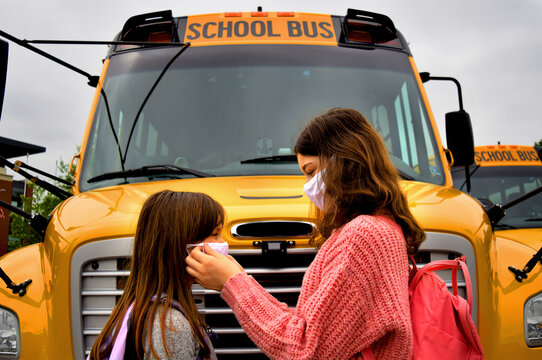 Children wearing face masks by school bus. Two girls helping with facemasks stand in front of a school bus. Education, medical, health, safety, back to school, and coronavirus concepts.