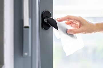 Poster Bar woman cleaning the doorknob with an alcohol disinfecting antibacterial wipe as a prevention to kill bacteria and viruses