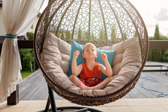 Staycation in summer cottage. Kid sitting in lotus yoga position near swimming pool