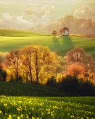 Wall Mural - Majestic rural landscape with an old mill. Beautiful sunlight on the wavy fields Kunkovice village.