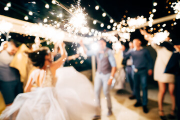 A close-up of the sparkler against the backdrop of the party.