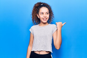 Beautiful kid girl with curly hair wearing casual clothes pointing thumb up to the side smiling happy with open mouth