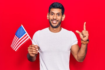 Young latin man holding united states flag smiling with an idea or question pointing finger with...